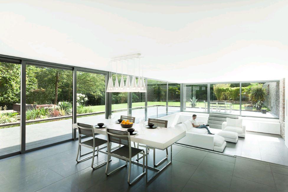 Mẫu phòng khách có thiết kế liền bếp với khung cửa kính nhìn ra sân vườn